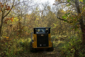 Forestry mulching is a method of clearing land using a single machine with a rotary drum (mulching head) equipped with steel chipper teeth to cut, grind, and shred vegetation.